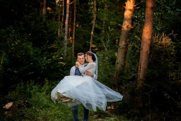 Piękni nowożeńcy pary odprowadzenie w lesie. nowożeńcy. panny młodej i pana młodego, trzymając rękę w lesie sosnowym, zdjęcie na walentynki