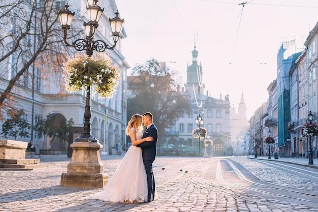 Piękni nowożeńcy przytulający się na rynku starego miasta