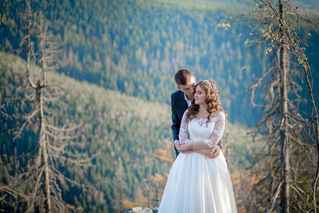 Piękni nowożeńcy ściska przeciw górom. stylowa panna młoda i piękna panna młoda stoją na klifie. portret ślubny. rodzinne zdjęcie