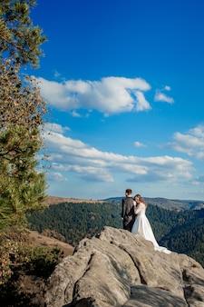 Piękni nowożeńcy ściska przeciw skałom i górom. stylowa panna młoda i piękna panna młoda stoją na klifie. portret ślubny. rodzinne zdjęcie