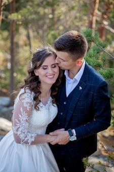 Piękni nowożeńcy ściskają na tle skał i gór. stylowa panna młoda i piękna panna młoda stoją na klifie. portret ślubny. rodzinne zdjęcie