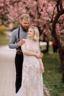 Piękni nowożeńcy ściskają się i uśmiechają na tle kwitnącego różowego kwiatu wiśni w słoneczny dzień. wiosenny ślub portret zbliżenie pana młodego i uroczej młodej blondynki.