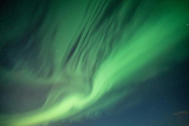 Piękni północni światła, zorz borealis tanczy na nocnym niebie