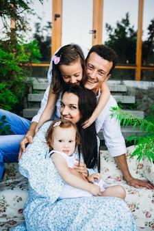 Piękni rodzice i ich małe dziewczynki siedzą na nogach na zewnątrz