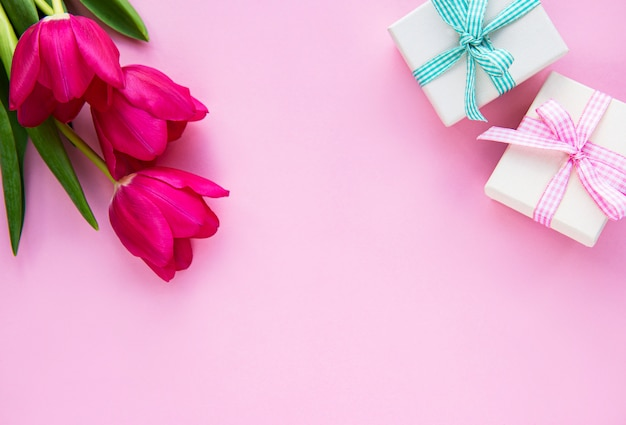 Piękni tulipanów bukieta i prezenta pudełka na różowym tle