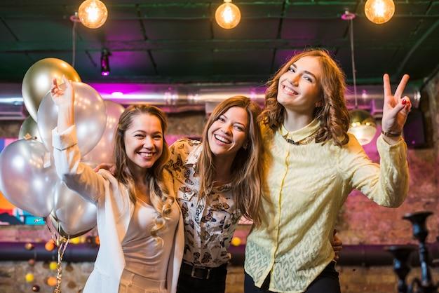 Piękni uśmiechnięci żeńscy przyjaciele cieszy się przyjęcia w noc klubie