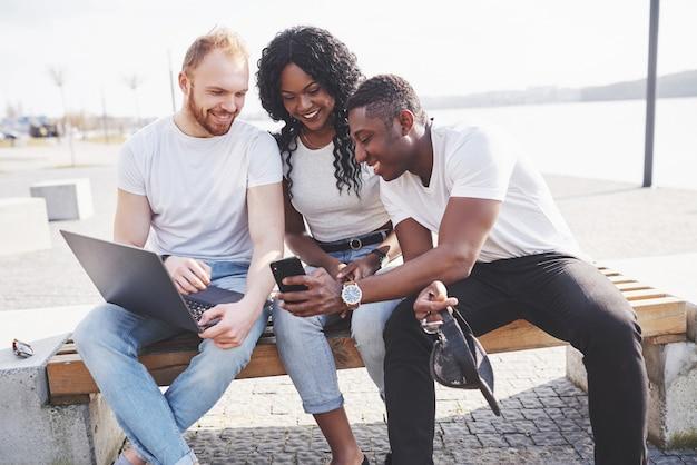 Piękni wielo- etniczni przyjaciele używa laptop na ulicie. koncepcja życia młodzieży