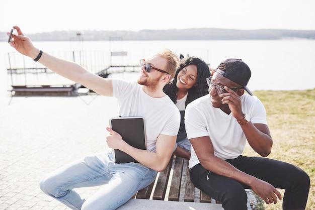 Piękni wielo- etniczni przyjaciele używa laptopu na ulicy i robią selphie. koncepcja życia młodzieży