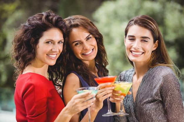 Piękni żeńscy przyjaciele trzyma koktajle