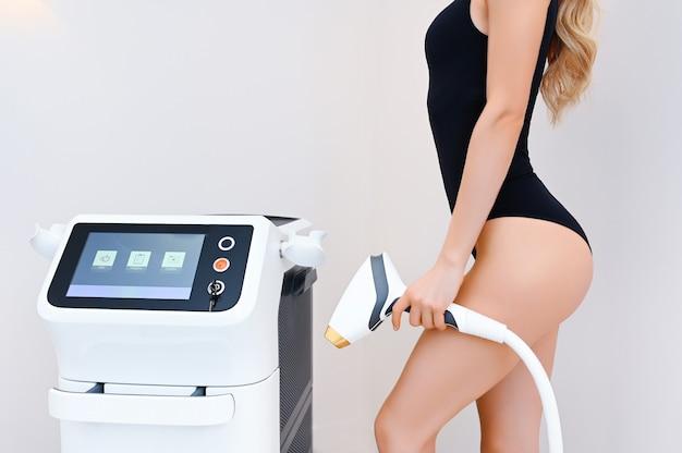 Pięknie dopasowane ciało kobiety o gładkiej miękkiej skórze w czarnej bieliźnie z urządzeniem laserowym w gabinecie kosmetycznym. depilacja i kosmetologia. koncepcja spa depilacji. wolne miejsce na baner tekstowy