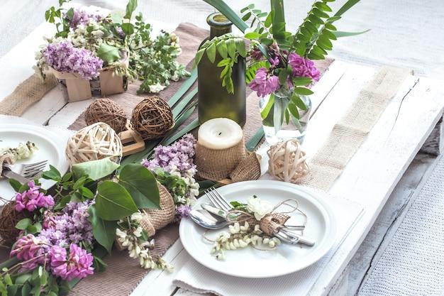 Pięknie elegancko udekorowany stół na wakacje z wiosennymi kwiatami i zielenią - wesele lub walentynki z nowoczesnymi sztućcami, kokardką, szkłem, świecą i prezentem, poziomy, zbliżenie, stonowany