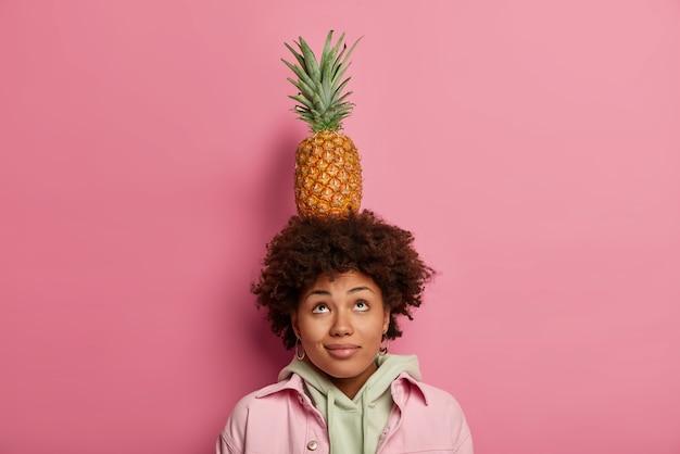 Pięknie kręcona kobieta wygląda powyżej, utrzymuje równowagę z ananasem na głowie, skoncentrowana powyżej, ma ciemną skórę i kręcone włosy, ubrana swobodnie, odizolowana na różowej ścianie. urocza samica niesie owoce tropikalne