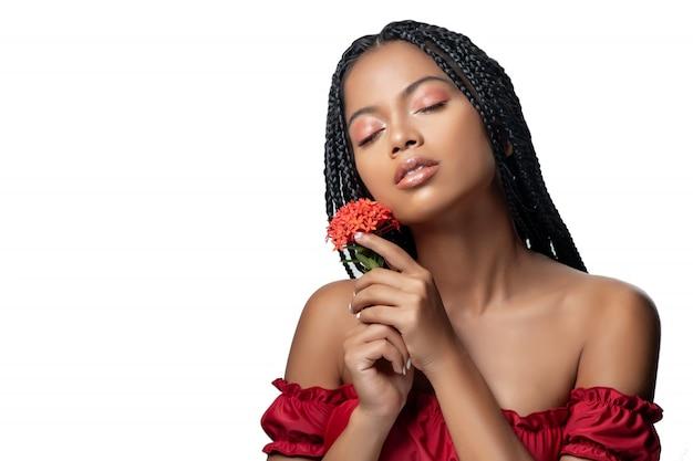 Pięknie mieszany biegowy piękno pozuje w czerwonej sukni z czerwonym kwiatem w jej ręce na bielu. na białym tle
