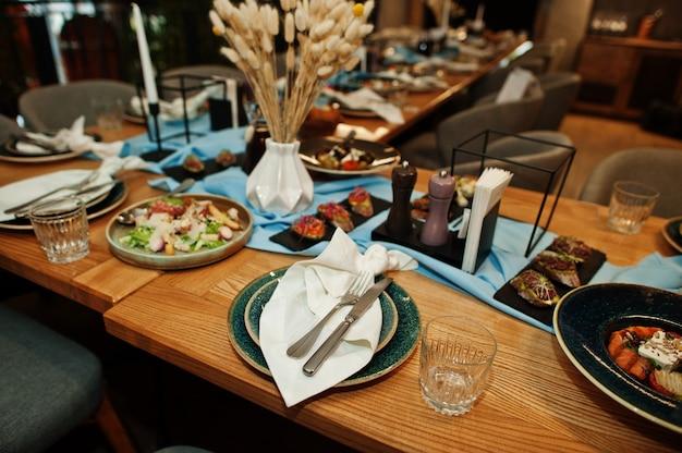 Pięknie nakryte stoły z jedzeniem, szklankami i sprzętem w restauracji.