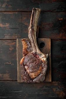 Pięknie obsmażony stek z tomahawka, średnio wysmażony na drewnianej desce do serwowania