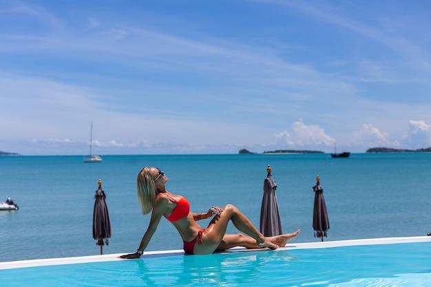 Pięknie opalona, dopasowana kaukaski kobieta z brązową błyszczącą skórą w bikini z olejem kokosowym