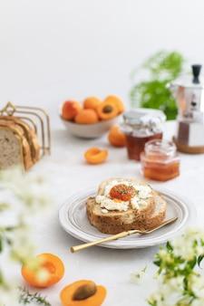 Pięknie podane letnie śniadanie z pieczywem tostowym i domowym dżemem morelowym