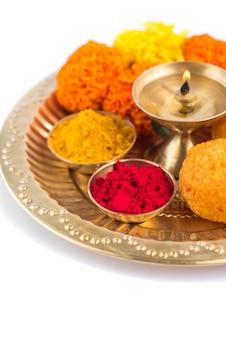 Pięknie udekorowane pooja thali na festiwalowe świętowanie kultu, haldi lub kurkuma w proszku i kumkum, kwiaty, pachnące patyczki w mosiężnym talerzu, hinduska pudża thali