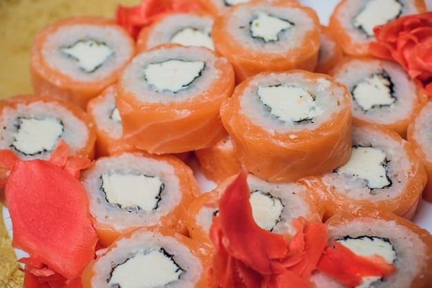 Pięknie udekorowane sushi na talerzu i pałeczki obok niego. sushi to tradycyjne azjatyckie i japońskie jedzenie. rolka sushi przygotowana z surowej ryby i specjalnego ryżu. dieta zdrowa żywność.
