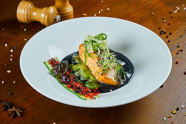 Pięknie udekorowany przez szefa kuchni pieczony łosoś z cukinią na poduszce cebuli z czarnymi tłuczonymi ziemniakami w białej misce na drewnianym stole. owoce morza z bliska.