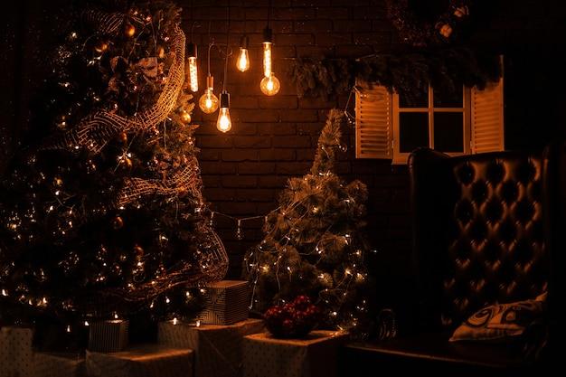 Pięknie udekorowany salon z choinką ze skórzanym fotelem vintage ze starymi żółtymi lampkami z prezentami bożonarodzeniowymi i zabawkami wieczorem.