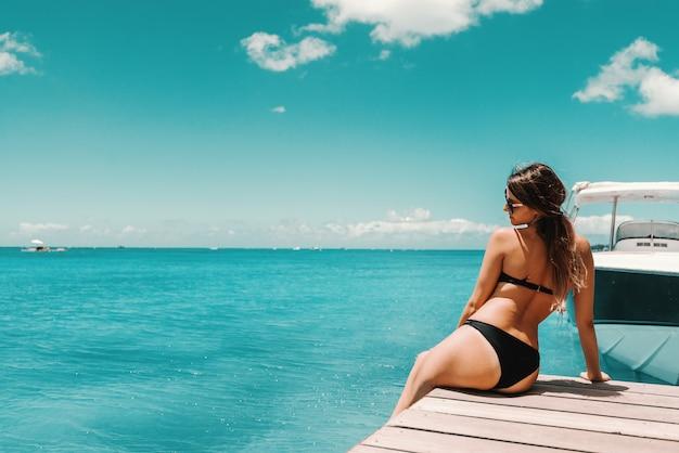 Pięknie ukształtowana brunetka w stroju kąpielowym i okularach przeciwsłonecznych siedzi na molo i cieszy się słoneczną pogodą i oceanem. z powrotem odwrócił się.