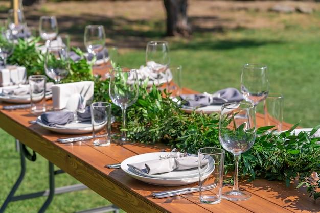 Pięknie urządzony drewniany stół w letniej kawiarni na świeżym powietrzu. dekoracja stołu zielona gałąź i świeżych kwiatów
