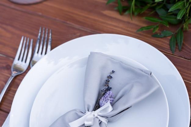 Pięknie urządzony drewniany stół w letniej kawiarni na świeżym powietrzu. dekoracja stołu zielona gałąź i świeżych kwiatów.