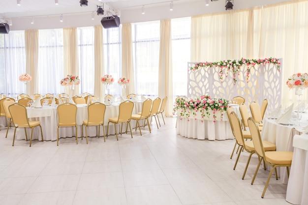 Pięknie urządzony pokój z zadaszonymi stołami z kwiatami w restauracji