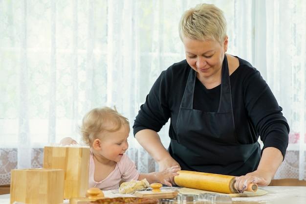 Pięknie uśmiechnięta dziewczynka pomaga babci rozwałkować ciasto.