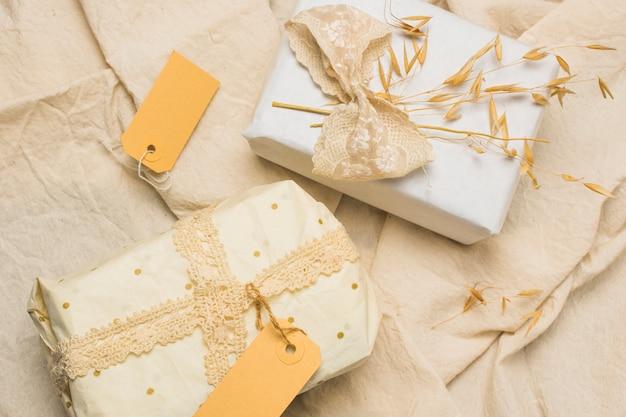 Pięknie zapakowane pudełka na prezenty z metkami na teksturowanej tkaninie