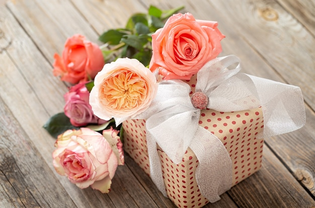 Pięknie zapakowany prezent i bukiet róż na rozmytym drewnianym stole.
