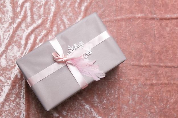 Pięknie zapakowany świąteczny i noworoczny prezent dla ciebie leży na puszystym kocu.