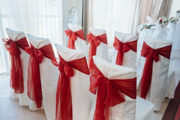 Pięknie zdobione i ustawione krzesła na uroczysty bankiet. dekoracje ślubne