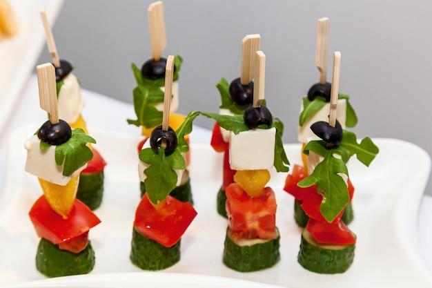 Pięknie zdobione przekąski na cateringowy stół bankietowy. catering na imprezy przekąski w formie bufetu