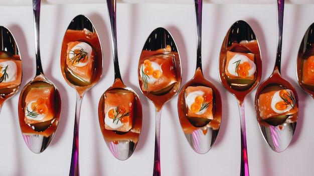Pięknie zdobiony stół bankietowy cateringowy z różnymi przekąskami i przystawkami z kanapkami, kawiorem, świeżymi owocami