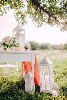 Pięknie zdobiony świąteczny stół w parku na zachodzie słońca, romantyczna kolacja weselna.
