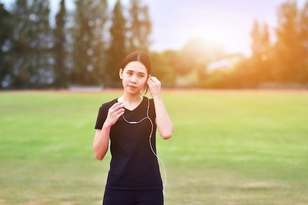 Piękno azjatyckie kobiety słucha muzykę podczas ćwiczenia biegającego ranek w miasto parku