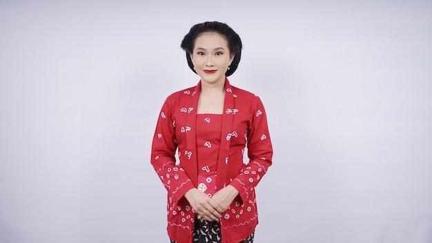 Piękno azjatyckiej czerwonej kebay uśmiecha się elegancko na białym tle