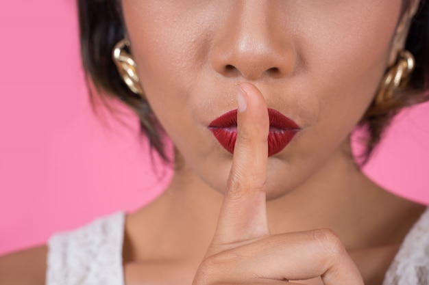 Piękno azjatykciej kobiety czerwone wargi i palec pokazuje ucichnięcie ciszy znaka