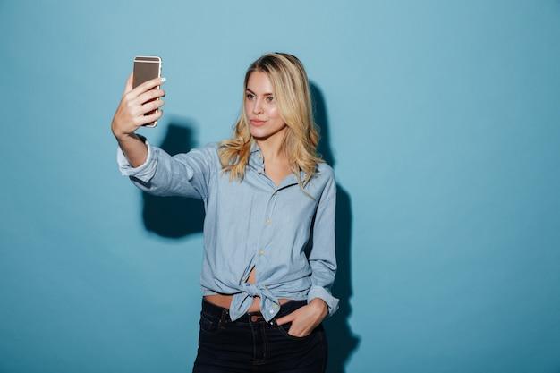 Piękno blondynki kobieta w koszula robi selfie na smartphone