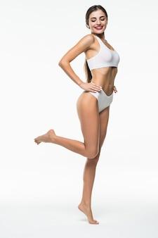 Piękno ciała kobiety, szczupły model spaceru w białej bieliźnie na białym tle nad białą ścianą