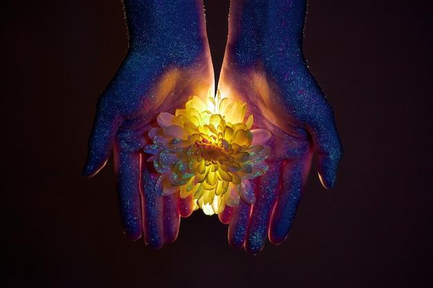 Piękno dłoni kobiety w świetle ultrafioletowym z kwiatami w dłoniach. kosmetyki do pielęgnacji skóry dłoni