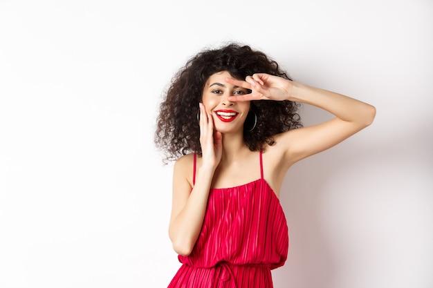 Piękno i moda. romantyczna kobieta z kręconymi włosami i czerwoną sukienką, pokazując znak v i uśmiechnięty szczęśliwy w aparacie, stojąc na białym tle.
