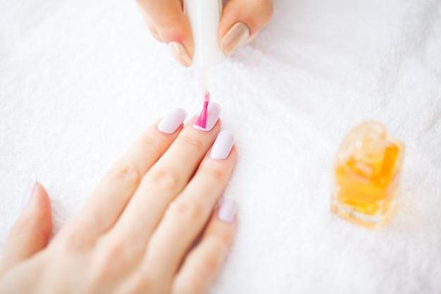 Piękno i pielęgnacja. mistrz manicure nakładający lakier do paznokci w salonie kosmetycznym. piękne damskie dłonie z doskonałym manicure. manicure spa