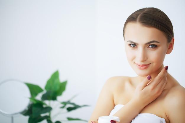 Piękno i pielęgnacja. szczęśliwa uśmiechnięta młoda kobieta trzyma krem do twarzy. dziewczyna po prysznic poranna pielęgnacja twarzy. gładka skóra.