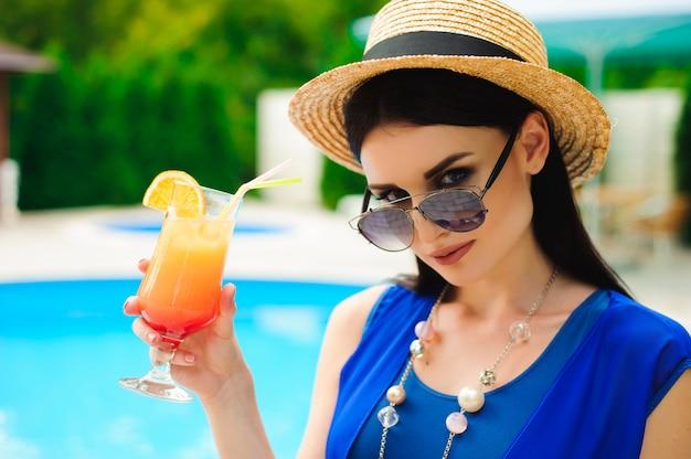 Piękno i wakacje. ładna młoda kobieta blisko pływackiego basenu.