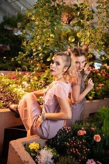 Piękno jest wszędzie. atrakcyjne stylowe kobiety patrzące na ciebie w otoczeniu kwiatów
