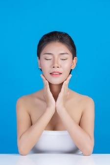 Piękno kobiet z doskonałymi obrazami zdrowia skóry dotykając jej twarzy i uśmiechając się jak spa, rozpieszczamy jej skórę niebiesko