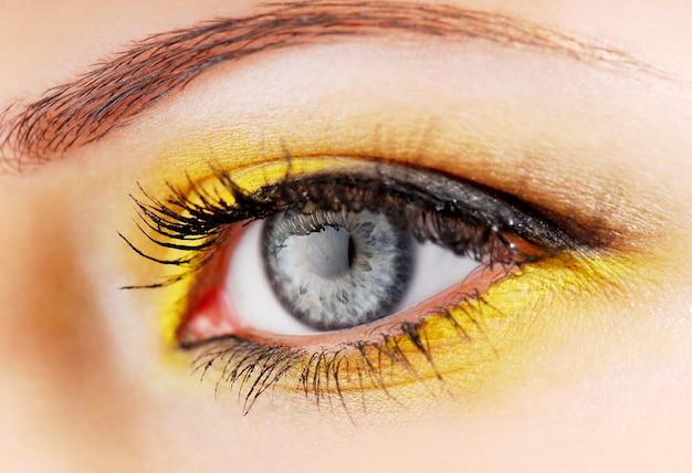 Piękno. kobieta oko z żółtym cieniem do powiek.